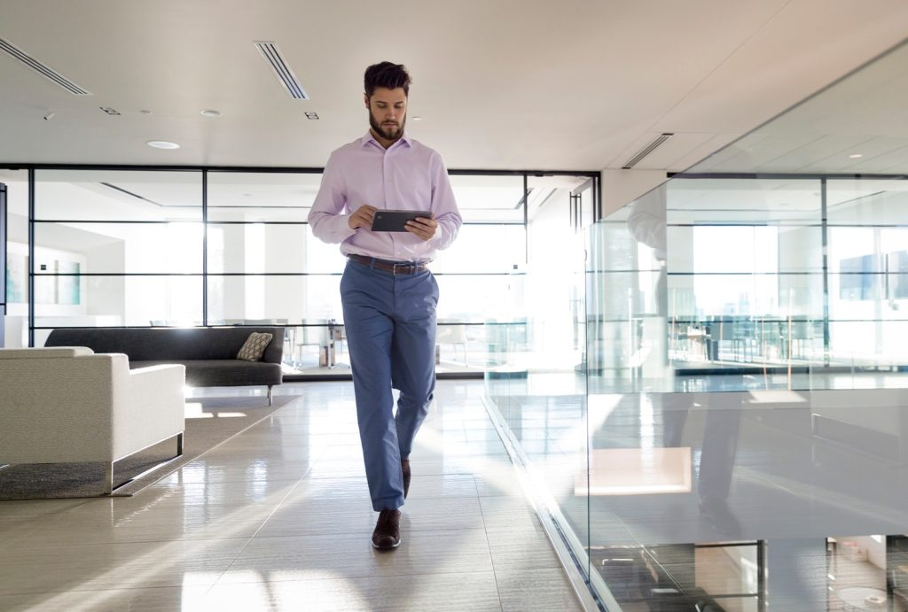 Man walking and using a tablet in an office