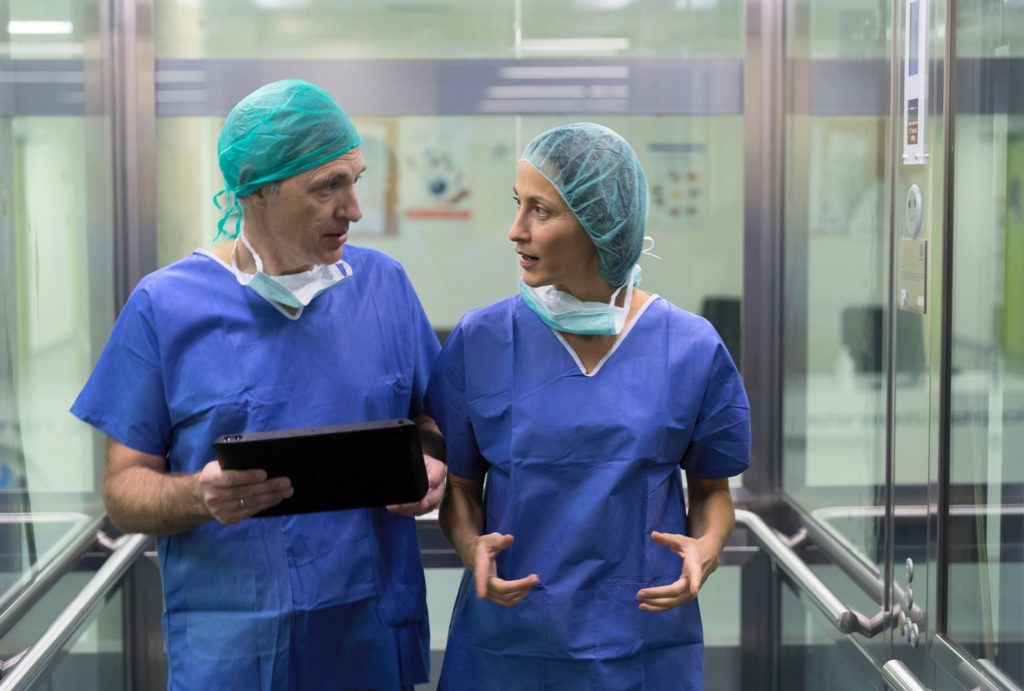 Surgeons using a tablet in the hospital elevator