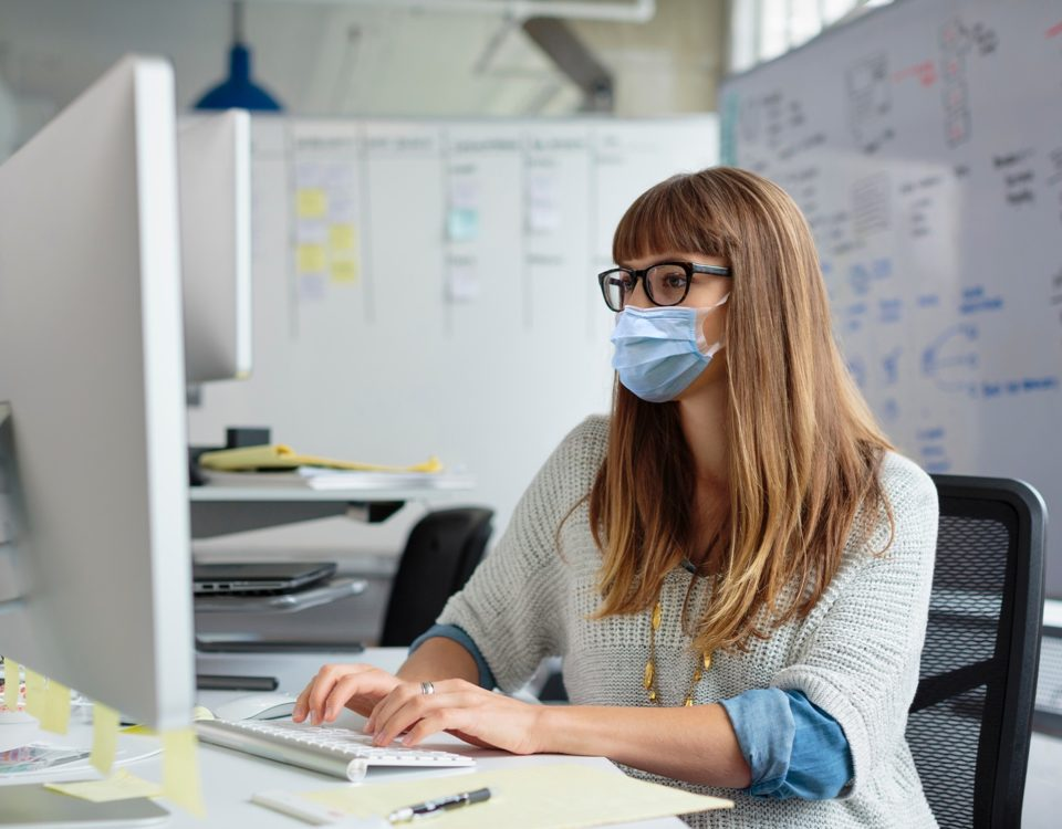 Serious casual woman typing on computer desktop keyboard at desk in open modern office